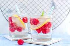 Homemade summer cold raspberry lemon cocktail with sparkling water and crushed iced in glasses Royalty Free Stock Photography