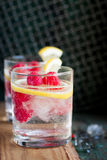 Homemade summer cold raspberry lemon cocktail with sparkling water and crushed iced in glasses on a vintage background Royalty Free Stock Photography