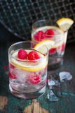 Homemade summer cold raspberry lemon cocktail with sparkling water and crushed iced in glasses on a vintage background. Closeup stock images