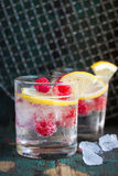 Homemade summer cold raspberry lemon cocktail with sparkling water and crushed iced in glasses on a vintage background Stock Photo