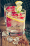 Homemade summer cold raspberry lemon cocktail with sparkling water and crushed iced in glasses on a vintage background Stock Image