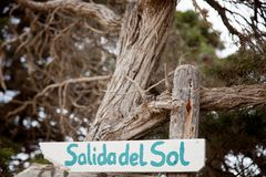 Homemade sunrise sign written in spanish made of wood on a background of branches stock photos