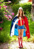 Homemade Super Hero. A girl in a home made super hero costume stands tall and confident. She has a tiara, lasso, cape and pretend boots. Red, white, and blue are Royalty Free Stock Photo