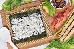 Homemade sushi food preparation with Nori algea sheet with rice on bamboo mat and ingredients like smoked salmon, avocado and egg