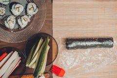 Homemade sushi. Male hands prepare rolls with rice, salmon, crab, cheese, nori, cucumber stock image