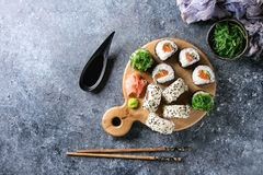 Sushi rolls set. Homemade sushi rolls set with salmon, sesame seeds serving on wood serving board with pink pickled ginger, soy sauce, wasabi, seaweed salad royalty free stock photo