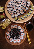 Homemade sushi rolls. Sticks, lemon, soy sauce, wasabi are served on a dark brown wooden table Royalty Free Stock Photography