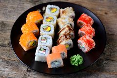 Homemade sushi with salmon, tobiko caviar, omelet, cucumber, sesame and soft cheese on old wooden background. Rustic style. Stock Images