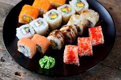 Homemade sushi with salmon, tobiko caviar, omelet, cucumber, sesame and soft cheese on old wooden background. Rustic style. Stock Image