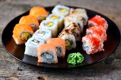 Homemade sushi with salmon, tobiko caviar, omelet, cucumber, sesame and soft cheese on old wooden background. Rustic style. Royalty Free Stock Photos