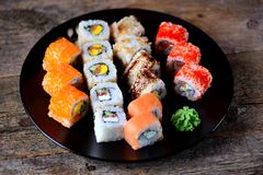 Homemade sushi with salmon, tobiko caviar, omelet, cucumber, sesame and soft cheese on old wooden background. Rustic style. Royalty Free Stock Photo