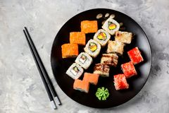 Homemade sushi with salmon, tobiko caviar, omelet, cucumber, sesame and soft cheese on old wooden background. Rustic style. Stock Photo