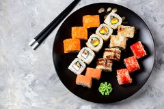 Homemade sushi with salmon, tobiko caviar, omelet, cucumber, sesame and soft cheese on old wooden background. Rustic style. Royalty Free Stock Images
