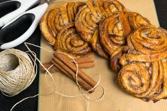 Homemade sweet cinnamon rolls on paper bag with sticks of cinnamons. Decorated with thread. Deserts Royalty Free Stock Photos