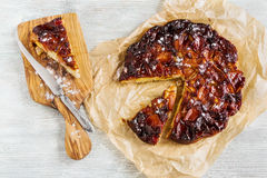 Homemade sweet fruit tart tatin on wooden background. Made with apples, glazed by caramel, sprinkled with powdered sugar. Top view Royalty Free Stock Image
