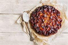 Homemade sweet fruit tart tatin on wooden background. Made with apples, glazed by caramel, sprinkled with powdered sugar. Top view Stock Photography