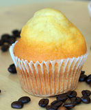 Homemade sweet muffin with coffee beans on a wooden table. Stock Photo