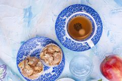 Homemade sweet muffins with almonds for breakfast. Tea and a glass of water in vintage blue dishes. Fruit and oil. Free space for stock photos
