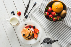 Homemade sweet pancakes and different fruits for healthy breakfast on wooden tabletop. Top view of homemade sweet pancakes and different fruits for healthy Stock Images