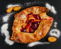 Homemade sweet plum open pie on black stone background royalty free stock photography