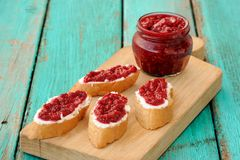 Homemade sweet raspberry jam in glass jar with four toasts with. Cream cheese and berry jam on wooden board on old turquoise table copyspace Stock Photography
