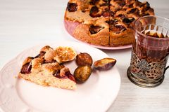 Homemade sweet round plum cake New York Times and cut n saucer with cups, glasses of tea, coffee on family holyday Breakfast or bi. Homemade sweet round plum royalty free stock photos
