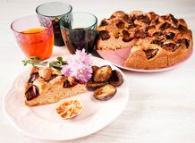 Homemade sweet round plum cake New York Times and cut n saucer with cups, glasses of tea, coffee on family holyday Breakfast or bi. Homemade sweet round plum royalty free stock photo
