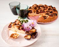 Homemade sweet round plum cake New York Times and cut n saucer with cups, glasses of tea, coffee on family holyday Breakfast or bi. Homemade sweet round plum royalty free stock image