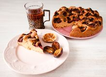 Homemade sweet round plum cake New York Times and cut n saucer with cups, glasses of tea, coffee on family holyday Breakfast or bi. Homemade sweet round plum royalty free stock images