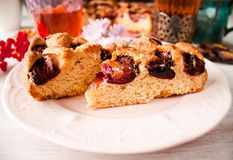 Homemade sweet round plum cake New York Times cuts on plate with cups, glasses of tea, coffee, flowers at back side on holyday Bre. Homemade sweet round plum stock photography