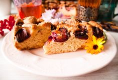 Homemade sweet round plum cake New York Times cuts on plate with cups, glasses of tea, coffee, flowers at back side on holyday Bre. Homemade sweet round plum stock photos