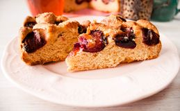 Homemade sweet round plum cake New York Times cutted on plate with cups, glasses of tea, coffee at back on holyday Breakfast or bi. Homemade sweet round plum royalty free stock images