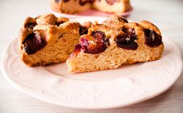 Homemade sweet round plum cake New York Times cutted on plate with cups, glasses of tea, coffee at back on holyday Breakfast or bi. Homemade sweet round plum stock photos