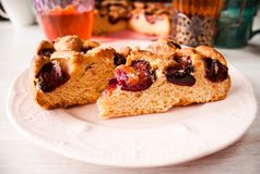 Homemade sweet round plum cake New York Times cutted on plate with cups, glasses of tea, coffee at back on holyday Breakfast or bi. Homemade sweet round plum stock photography