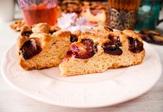 Homemade sweet round plum cake New York Times cutted on plate with cups, glasses of tea, coffee at back on holyday Breakfast or bi. Homemade sweet round plum stock photo