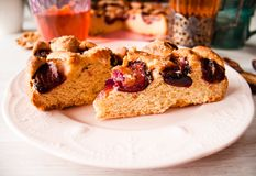 Homemade sweet round plum cake New York Times cutted on plate with cups, glasses of tea, coffee at back on holyday Breakfast or bi. Homemade sweet round plum royalty free stock photo