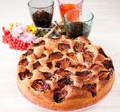 Homemade sweet round plum cake New York Times on plate with of tea coffee cup and flowers on family Breakfast or birthday holyday. Party on white vintage table stock photo