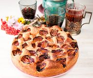 Homemade sweet round plum cake New York Times on plate with of tea coffee cup and flowers on family Breakfast or birthday holyday. Party on white vintage table royalty free stock photo