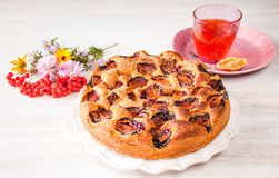 Homemade sweet round plum cake New York Times on plate with of tea, coffee cup and flowers on family Breakfast or birthday holyday. Party on white vintage table royalty free stock photos