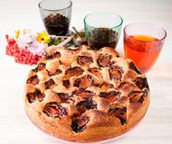 Homemade sweet round plum cake New York Times on plate with of tea coffee cup and flowers on family Breakfast or birthday holyday. Party on white vintage table stock photography