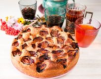 Homemade sweet round plum cake New York Times on plate with of tea coffee cup and flowers on family Breakfast or birthday holyday. Party on white vintage table royalty free stock photos