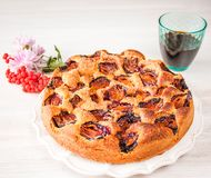 Homemade sweet round plum cake New York Times on plate with of tea, coffee cup and flowers on family Breakfast or birthday holyday. Party on white vintage table royalty free stock images