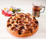 Homemade sweet round plum cake New York Times on plate with of tea coffee cup and flowers on family Breakfast or birthday holyday. Party on white vintage table stock photos
