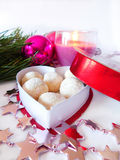 Homemade sweets in a box. Homemade sweets covered with coconut flakes are lying in the heart-shaped box stock photo