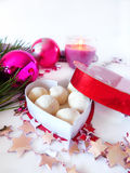 Homemade sweets in a box. Homemade sweets covered with coconut flakes are lying in the heart-shaped box royalty free stock image