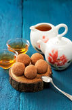 Homemade sweets in cocoa powder on oak board with tea and teapot Royalty Free Stock Photos