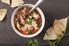 Homemade Taco Soup above shot. Homemade Taco Soup in small white bowl with crushed tortilla chips on dark wooden background above shot Stock Photo
