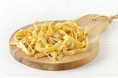 Homemade tagliatelle on chopping board on wooden white background stock photo