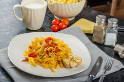 Homemade tagliatelle with garlic and cherry tomatoes Royalty Free Stock Image