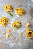 Homemade tagliatelle pasta nest, parmesan and basil Stock Photo